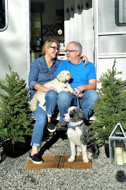 man and woman sitting in doorway of RV with two dogs