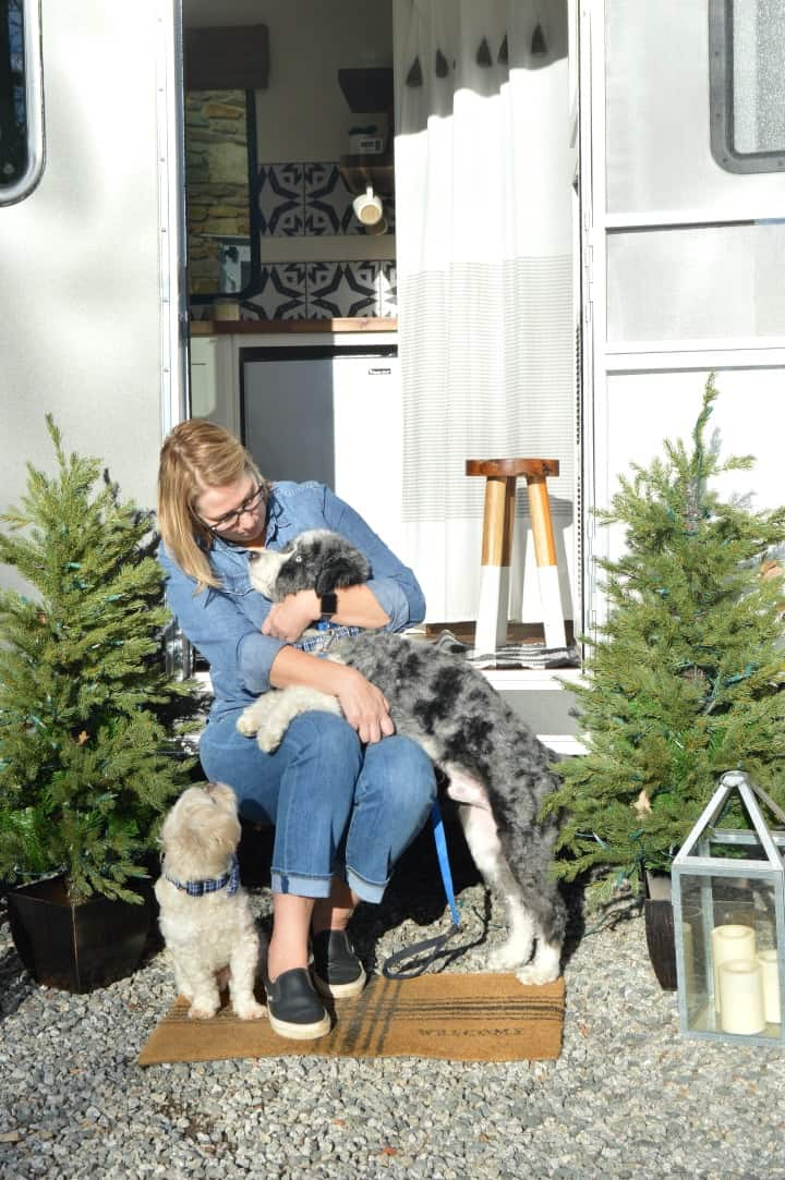 woman and two dogs sitting in doorway of RV