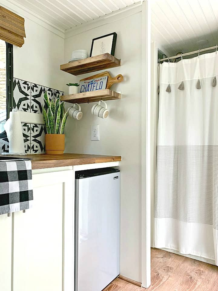 RV kitchen corner with wood shelves for storage that hold dishes and a picture