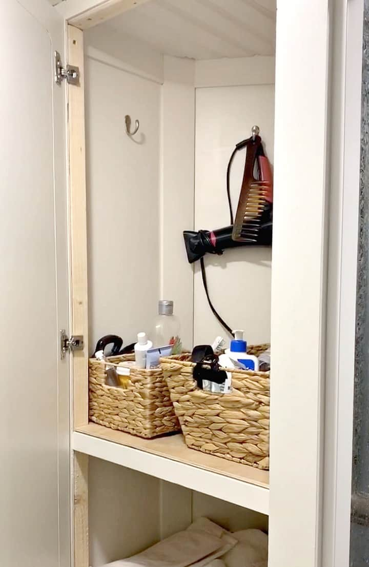 woven baskets in RV linen closet used for toiletry organization