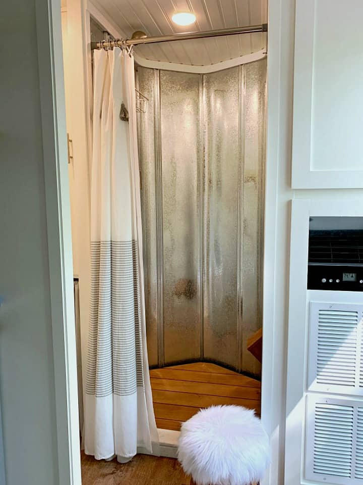 RV shower with metal walls and wood floor mat