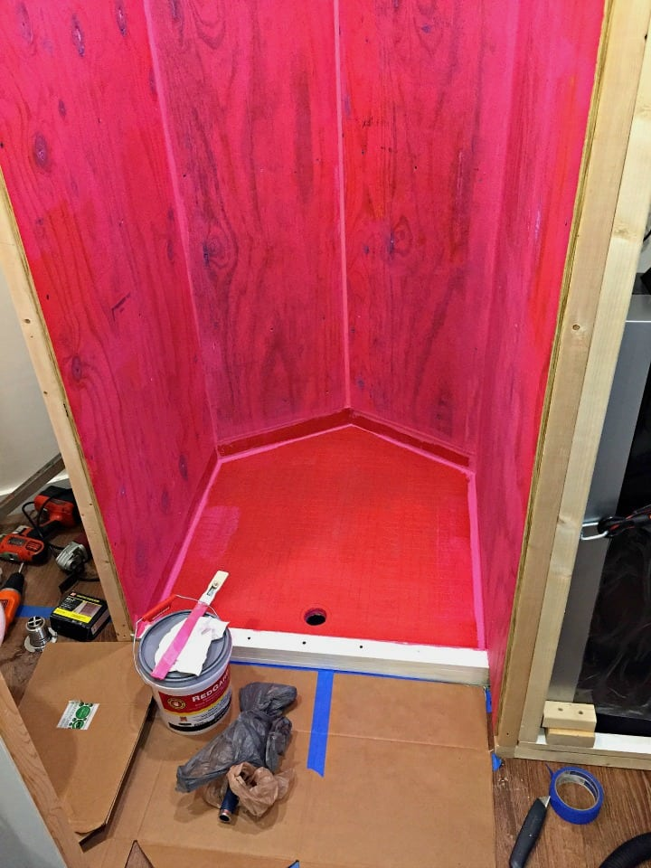 custom built shower in cargo trailer conversion with waterproof walls in red