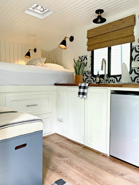 white kitchen and bed view in cargo trailer conversion
