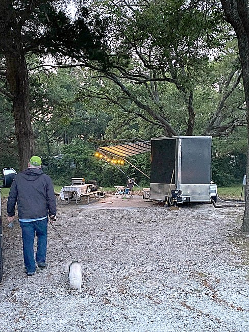 man in green hat walking dog at campsite with dark gray cargo trailer