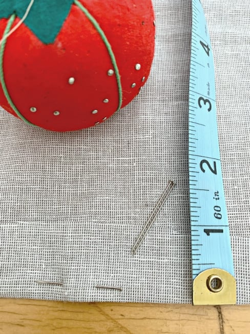 tape measure and straight pins on piece of curtain fabric