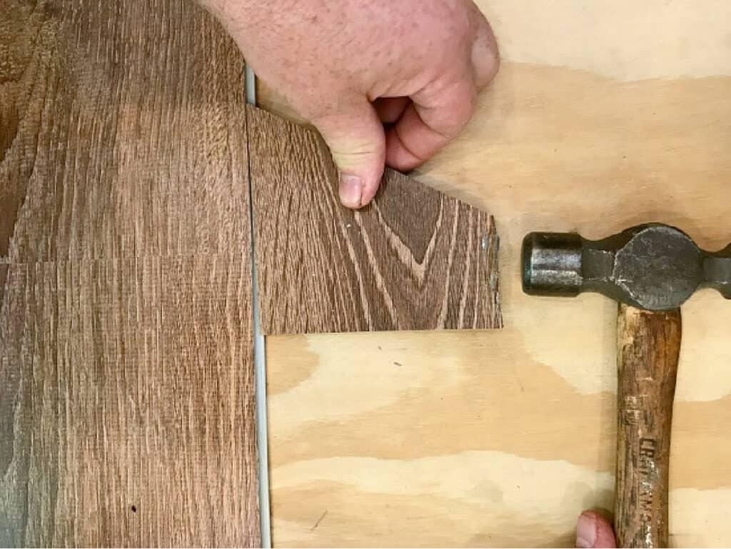 using a hammer to install vinyl plank floor